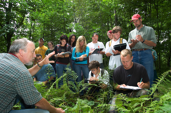 students in a forest taking notes on plants